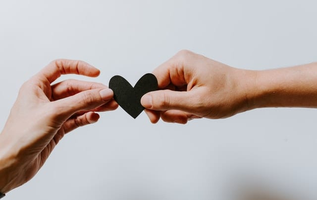 photo of two hands holding a black paper heart