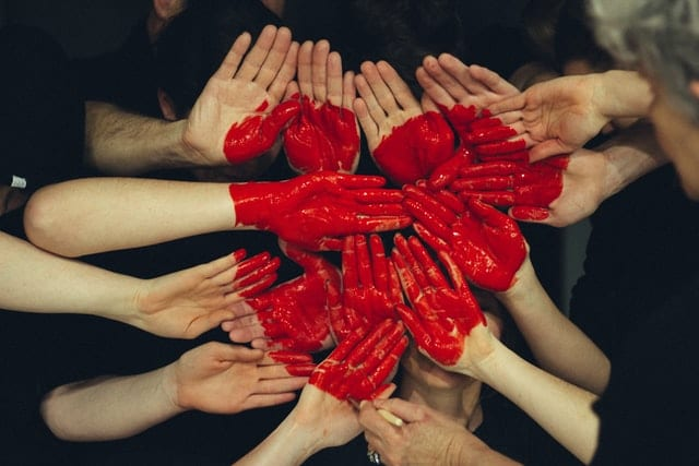 image of a group of hand, with a red heart painted in the middle