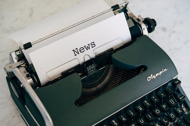 """image of a green typewriter with a paper that says """"news"""""""