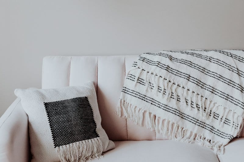 a sofa with pillow and blanket